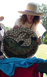 BCI Outreach volunteer with stone mosaics made at Bowker Creek celebration events